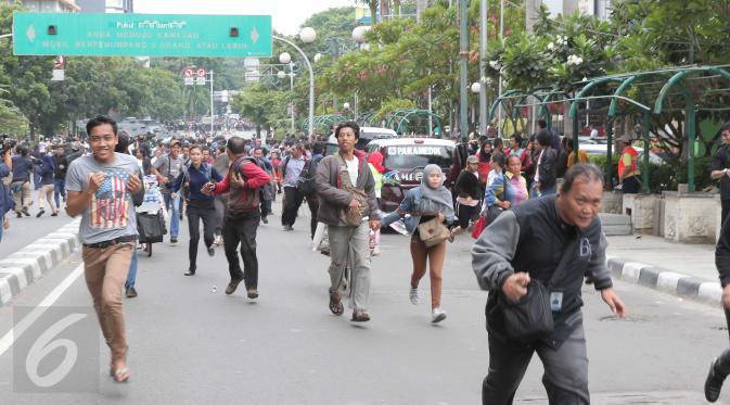 Seorang jurnalis (kanan) bersama sejumlah warga berlarian usai mendengar isu bom yang akan kembali meledak pasca ledakan yang terjadi di Pos polisi dekat pusat perbelanjaan Sarinah, Jalan Thamrin, Jakarta, Kamis (14/1). (Liputan6.com/Angga Yuniar)