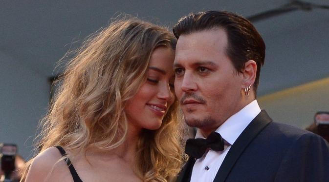 Aktor Johnny Depp dan Amber Heard saat menghadiri pemutaran film 'Black Mass' di Festival Film Venezia, Italia, 4 September 2015. Amber Heard menggugat cerai Johnny Depp karena perbedaan yang tak bisa diatasi selama 15 bulan pernikahan. (Tiziana FABI/AFP)