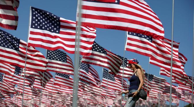 Seorang wanita berjalan diantara 3.000 bendera AS pada peringatan 15 tahun bagi para korban 11 September 2001 di Malibu, California, (11/09). Pengibaran bendera AS dilakukan sejak matahari terbit sampai terbenam. (REUTERS/Lucy Nicholso)