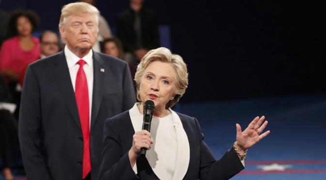 Hillary Clinton saat menjawab pertanyaan penonton dalam debat Capres AS putaran kedua, St Louis, AS, Minggu (9/10). Terlihat di belakang Hillary, Trump berekspresi aneh yang menjadi bahan ejekan di media sosial. (REUTERS/Rick Wilking)