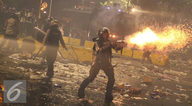 Polisi menembakkan gas air mata ke arah pendemo saat bentrok di Jakarta, Jumat (4/11). Diduga bentrok terjadi saat massa HMI menyerang polisi dan polisi membalasnya dengan melempar gas air mata. (Liputan6.com/Immanuel Antonius)