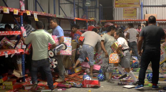Sejumlah orang menjarah berbagai produk mainan di sebuah toko di negara bagian Veracruz, Meksiko, Rabu (4/1). Penjarahan terjadi di sejumlah toko di Meksiko, seiring berlangsungnya unjuk rasa memprotes kenaikan harga bahan bakar minyak. (Ilse HUESCA/AFP)