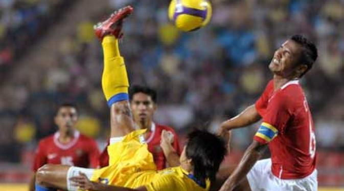 Thai football player Suchao Nutnum (L) over-head kicks the ball next to Charis Yulianto (R) of Indonesia during their AFF Suzuki Cup 2008 at Rajamangala stadium in Bangko/PORNCHAI KITTIWONGSAKUL